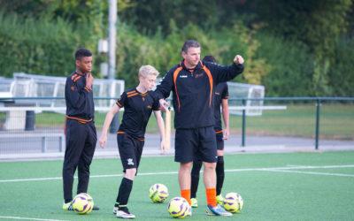 Sportpsycholoog in trainingspak samen met de coach op het veld.